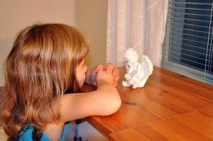 En enfant prie face à un petit ange